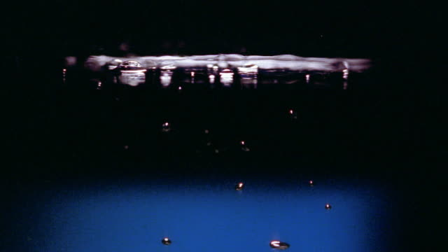Small bubbles then large bubbles rising to surface of water with blue background