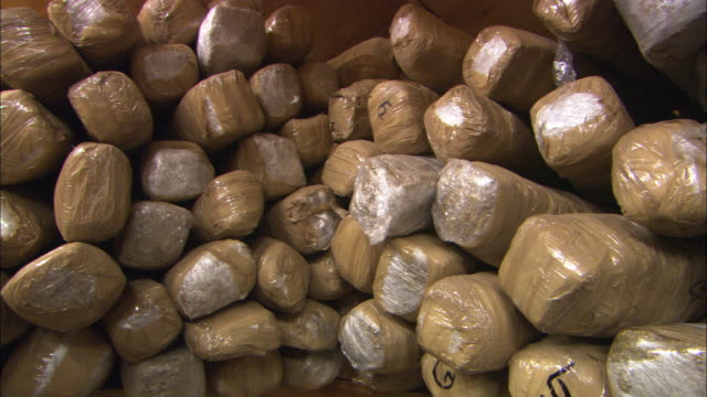 small bundles of illegal drugs are piled in an evidence room. - mexico stock videos & royalty-free footage