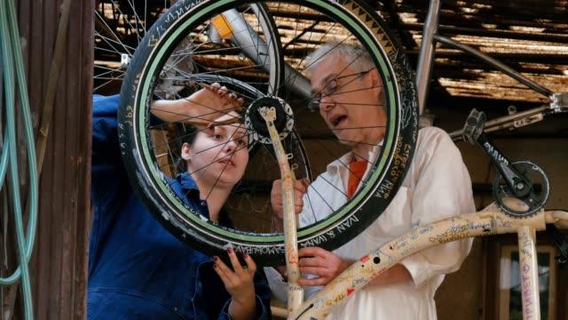 vidéos et rushes de petites entreprises. couple monter à bicyclette. travailler ensemble. art et artisanat produit - objet manufacturé