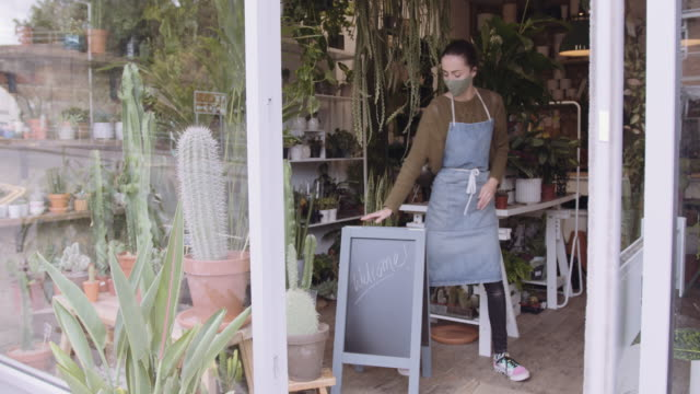 small business entrepreneur female opening plant shop with welcome sign wearing face mask during coronavirus pandemic - fioraio negozio video stock e b–roll