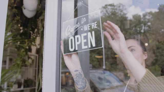 small business entrepreneur store owner turning open sign in shop doorway window - store opening stock videos & royalty-free footage