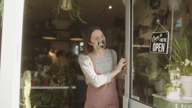 small business entrepreneur wearing face mask open store door for customers during coronavirus pandemic. - epidemic stock videos & royalty-free footage