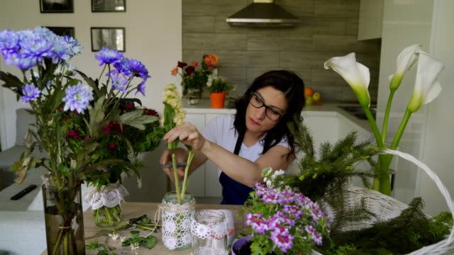 small business. mature woman  florist .floral design studio at home, making decorations and arrangements. flowers delivery - craft stock videos & royalty-free footage