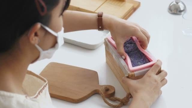 vidéos et rushes de petite entreprise de femme asiatique fait un savon bio avec processus de coupe lors de l'utilisation dur en bois pain de savon cutter outils handmade précision coupe savon faucheuse son savon dans sa chambre - artisant