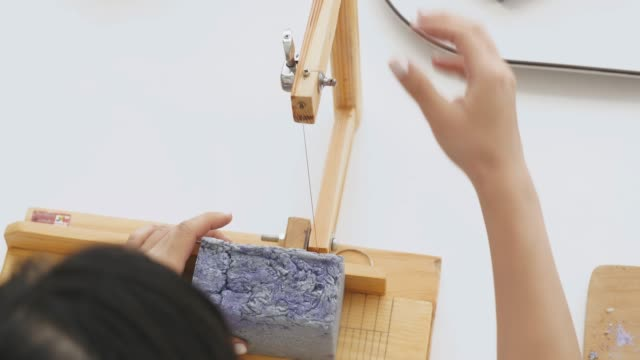 small business of asian woman is making organic soap with process of cutting while using hard wooden loaf soap cutter tools handmade precision cutting soap trimming  her handmade soap at her room - hobby video stock e b–roll