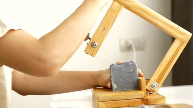 Small business of Asian woman is making organic soap with process of cutting while using Hard Wooden Loaf Soap Cutter Tools Handmade Precision Cutting Soap Trimming  her handmade soap at her room