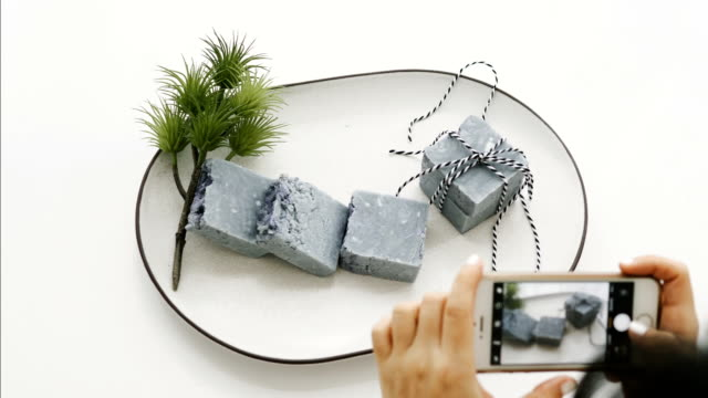 Small business of Asian woman is taking a picture of organic soap by using smart phone  with process of design artwork or production and create a picture for sale online or e-commerce-craft and homemade small business concept