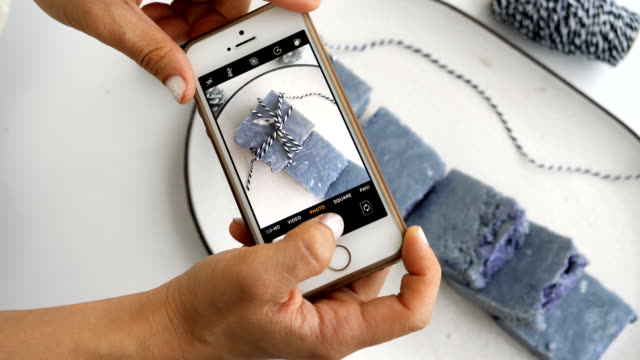 vídeos y material grabado en eventos de stock de pequeña empresa de la mujer asiática es tomar una foto de jabón orgánico mediante el uso de teléfonos inteligentes con el proceso de diseño de arte o la producción y crear una imagen para la venta en línea o e-commerce-arte y concepto de pequeña empresa casera - hecho en casa