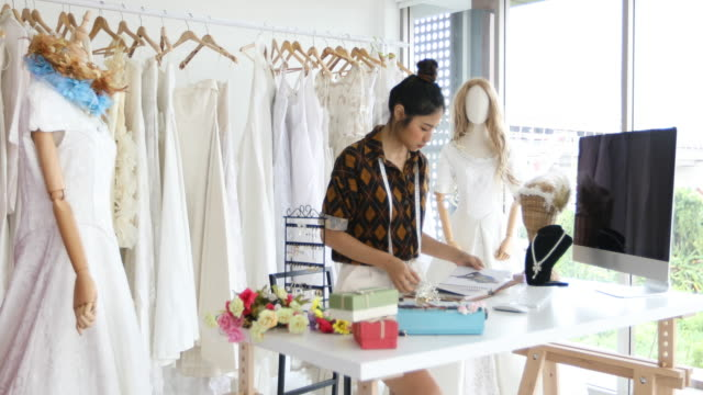 small business of asian women fashion designer working and using smart phone and tablet with wedding dresses at at clothing store - fashion designer stock videos and b-roll footage