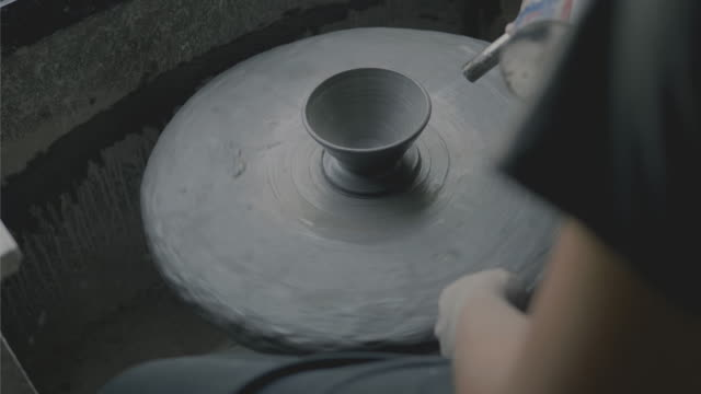 small business of craft ceramic;close up of hands of a potter, creating a cup on the circle wheel while using fire spray foam- stock video - prodotti in ceramica video stock e b–roll