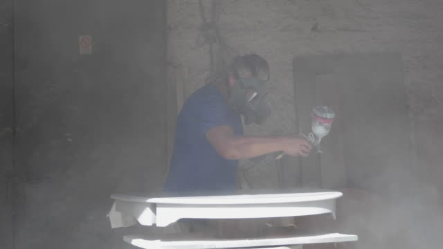 small business of mature man. restoration of old wooden furniture in workshop. man spray painting furniture with gas mask on - airbrush stock videos & royalty-free footage