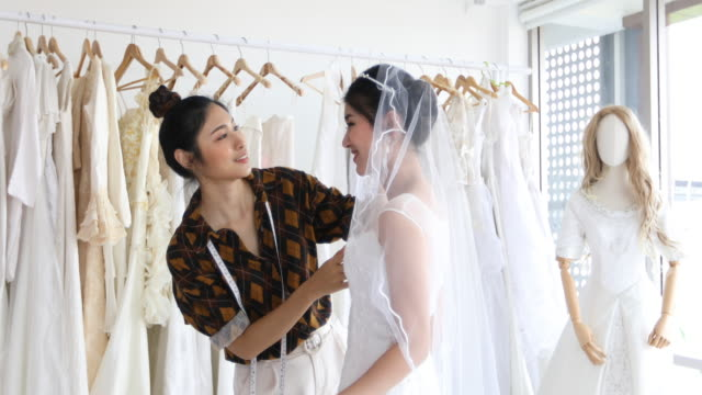 small business of young beautiful asian bride woman is standing in front of mirror and fitting dress in atelier with fashion designer for wedding at clothing store - designer clothing stock videos & royalty-free footage