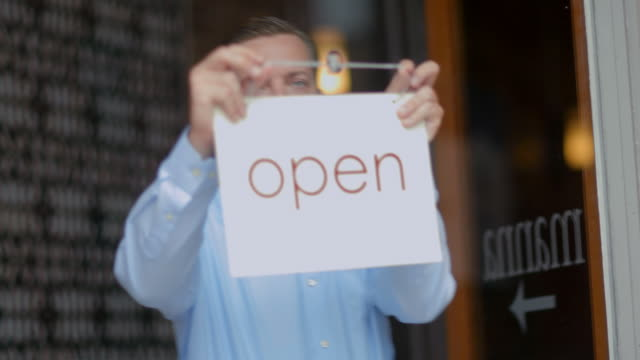 Small business owner hangs Open sign on door