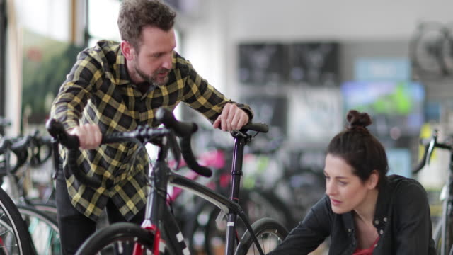 Small business owner helping customer in a bike store