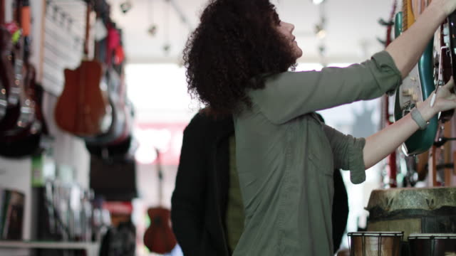 vidéos et rushes de small business owner helping customer in a guitar store - vendeur