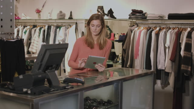 small business owner in clothes shop working on digital tablet - clothes shop stock videos and b-roll footage