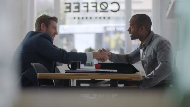 ms. small business owner meets and shakes hands with financial advisor in local coffee shop. - ansikte mot ansikte bildbanksvideor och videomaterial från bakom kulisserna