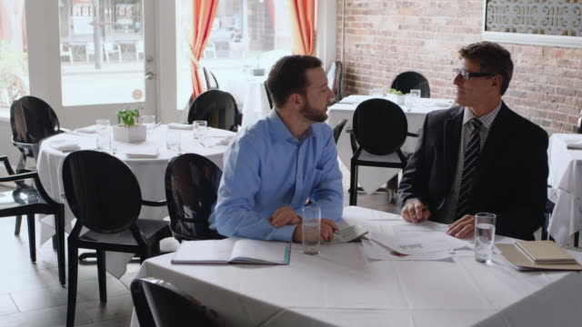 small business owner meets with financial advisor in restaurant - gastwirt stock-videos und b-roll-filmmaterial