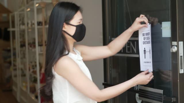 stockvideo's en b-roll-footage met small business eigenaar heropening winkeldeuren na covid-19 lockdown - heropening