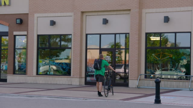 small business owner rides up to shop on bike and walks into store - centro commerciale suburbano video stock e b–roll