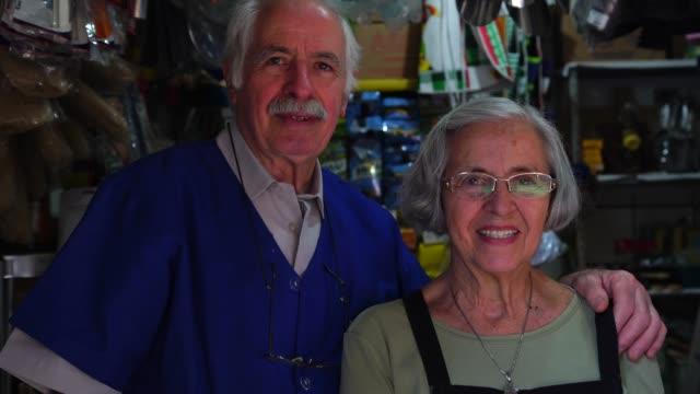 vídeos de stock, filmes e b-roll de retrato de casal sênior de proprietário pequenos negócios - trabalho comercial