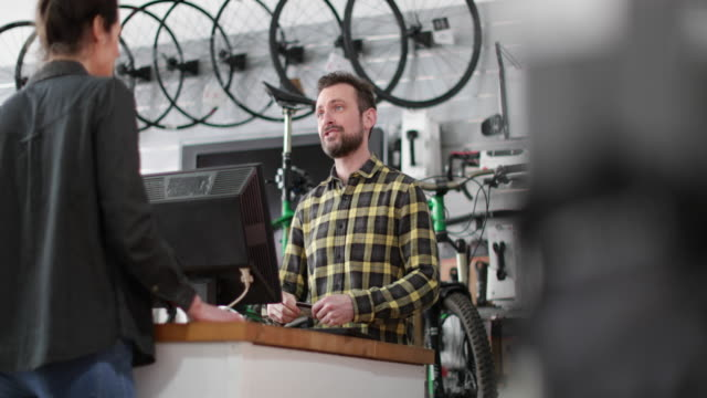 small business owner serving customer in a bicycle store - charging sports stock videos & royalty-free footage