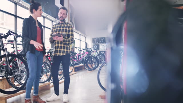 small business owner serving customer in a bike store - serving sport stock videos and b-roll footage