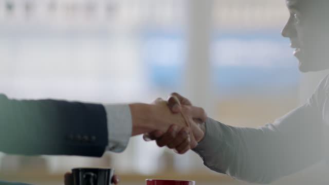 vídeos de stock, filmes e b-roll de ms slo mo. small business owner shakes hands with accountant over coffee in local coffee shop. - dando a mão