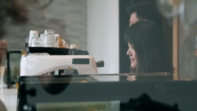 vídeos y material grabado en eventos de stock de dueño de negocio pequeño de pie en el mostrador de la cafetería. - cafeteria