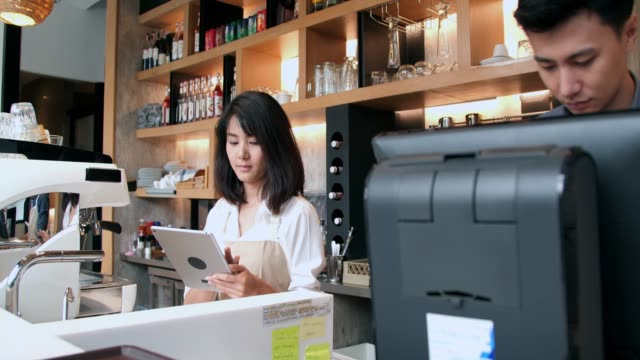 Small business owner standing at counter in coffee shop.