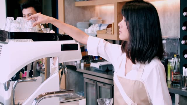 Small business owner standing at counter in coffee shop. woman barista making coffee at bar in cafe.