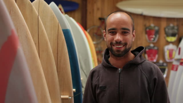 small business owner standing in surf shop smiling at camera - one mid adult man only stock videos & royalty-free footage