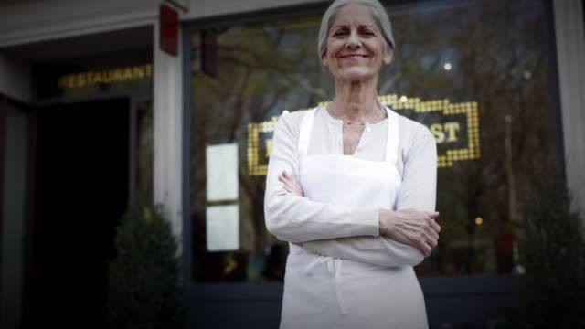 vidéos et rushes de ms small business owner standing outside her restaurant with her arms crossed / new york city, new york, usa - entrepreneur