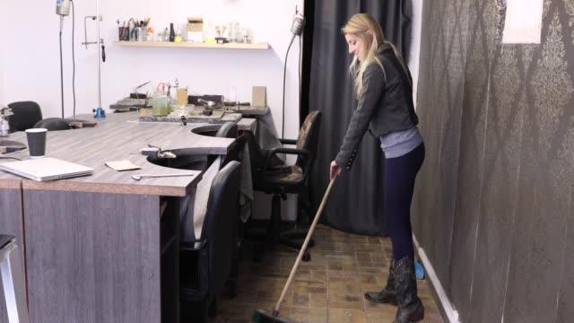 vídeos de stock, filmes e b-roll de um pequeno empresário varrendo o chão em sua oficina. - só uma mulher de idade mediana