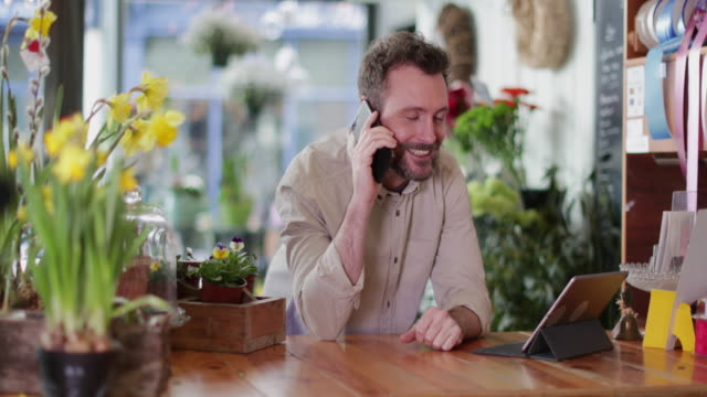 small business owner using digital tablet and smartphone in a florist - florist stock videos and b-roll footage