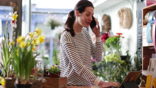 vidéos et rushes de small business owner using digital tablet and smartphone in a florist - client