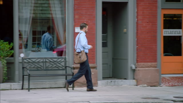 small business owner walks up downtown sidewalk and unlocks restaurant - eintreten stock-videos und b-roll-filmmaterial