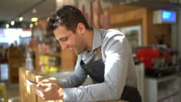 Small business owner watching sports using mobile phone inside his store