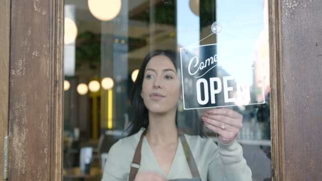 small business owner woman in apron hanging open sign on door - hanging stock videos & royalty-free footage