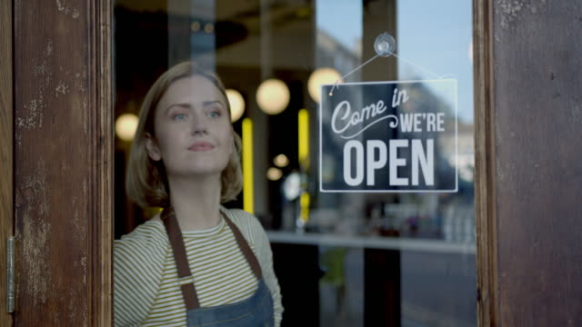 small business owner woman in apron hanging open sign on door - building entrance stock videos & royalty-free footage