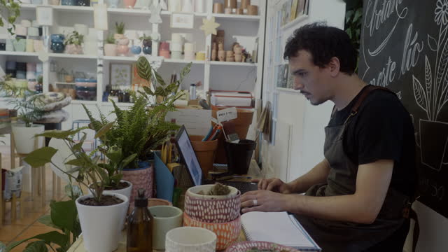 stockvideo's en b-roll-footage met kleine bedrijfseigenaar die aan laptop in zijn plantkundeboetiek werkt - elektronische handel