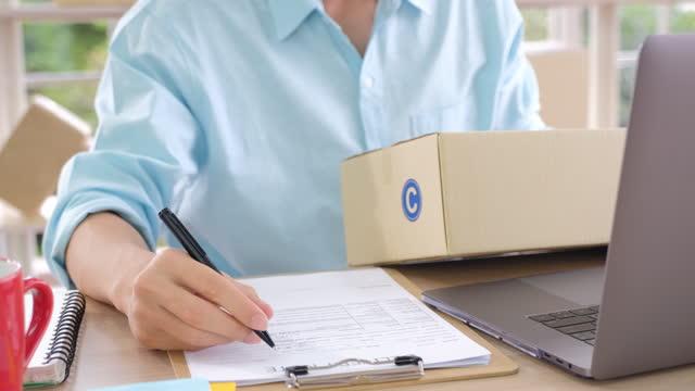 småföretag startar ägare som arbetar på hemmakontor med dator, frilansande man säljare kontrollera produktorder för leverans från online säljer e-handel - e post bildbanksvideor och videomaterial från bakom kulisserna