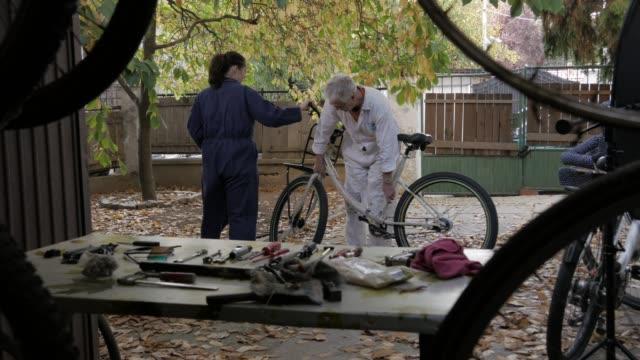kleine unternehmen. zusammen arbeiten. paar montieren fahrrad. kunst und handwerk produkt - dokumentarfilmmaterial stock-videos und b-roll-filmmaterial