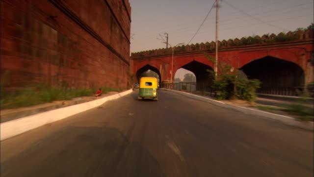 a small cab drives swiftly down a delhi street. - delhi stock videos & royalty-free footage