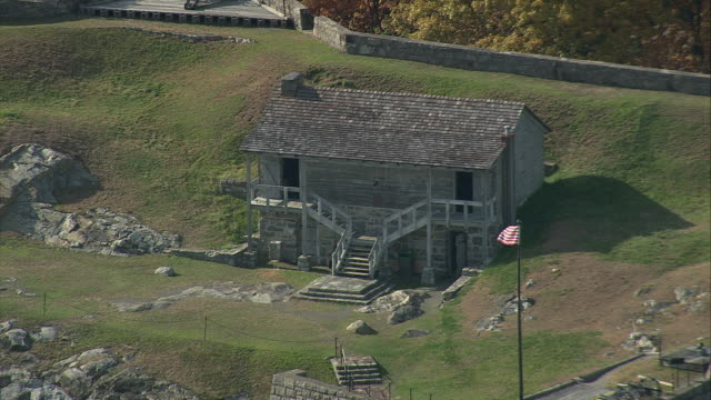 aerial small cabin surrounded by stone walls sitting among trees / west point, new york, united states - west point new york stock videos & royalty-free footage