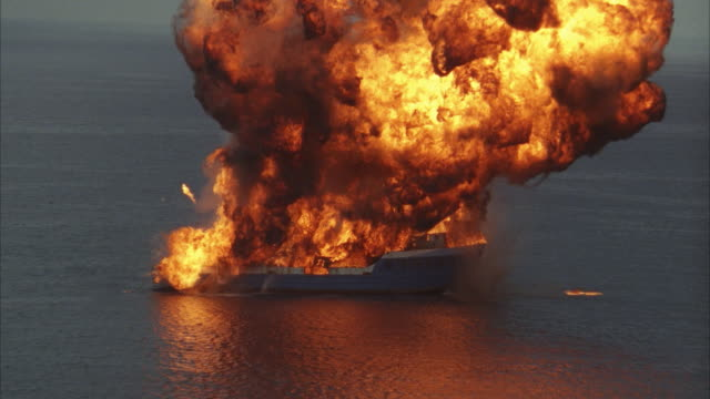 aerial, pan small cargo ship exploding on sea - nautical vessel stock videos & royalty-free footage