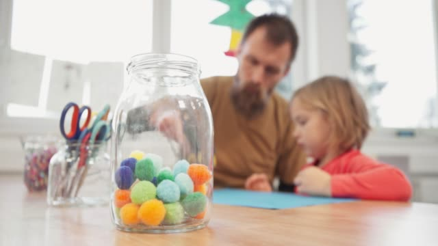 vídeos de stock e filmes b-roll de small child creating art out of colored cotton balls - edifício de infantário