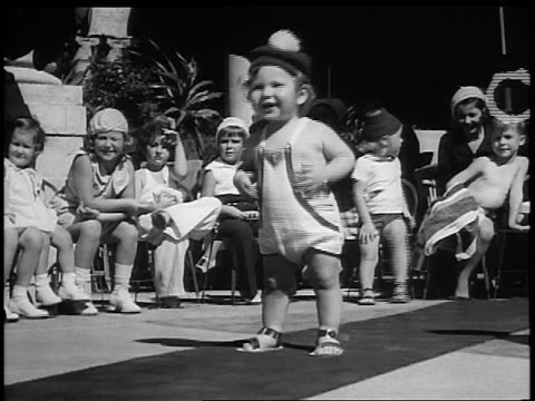B/W 1936 small child dancing in outfit cap in children's fashion show outdoors / Miami / newsreel
