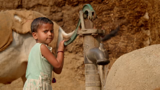 a small child uses a water pump in a village in bihar, india. - sötvatten bildbanksvideor och videomaterial från bakom kulisserna