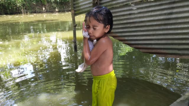 a small child washes herself with a cloth whilst bathing in a pond beside her corrugated iron house on june 14 2020 afrin 4 years old is normally a... - tradizione video stock e b–roll